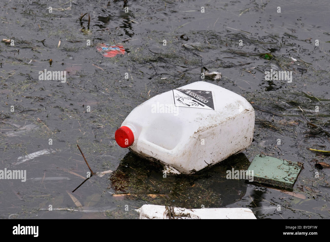 Dirty water, old canister with corrosive substances floating on dirty film - Stock Image