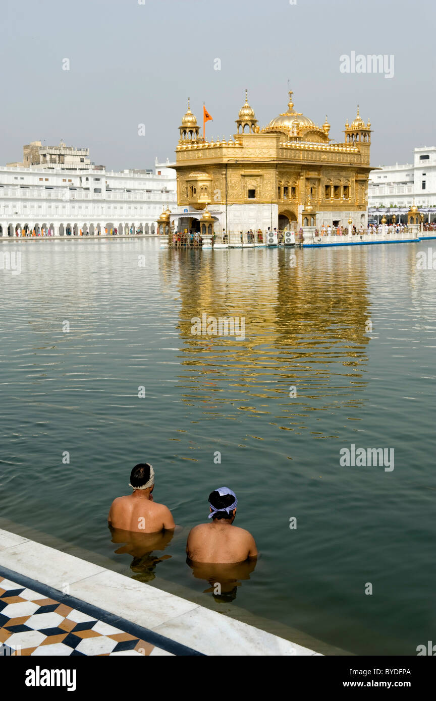Sikhism, ritual washing, two believers of the Sikh taking a ritual bath in the lake, sacred Golden Temple, Hari - Stock Image