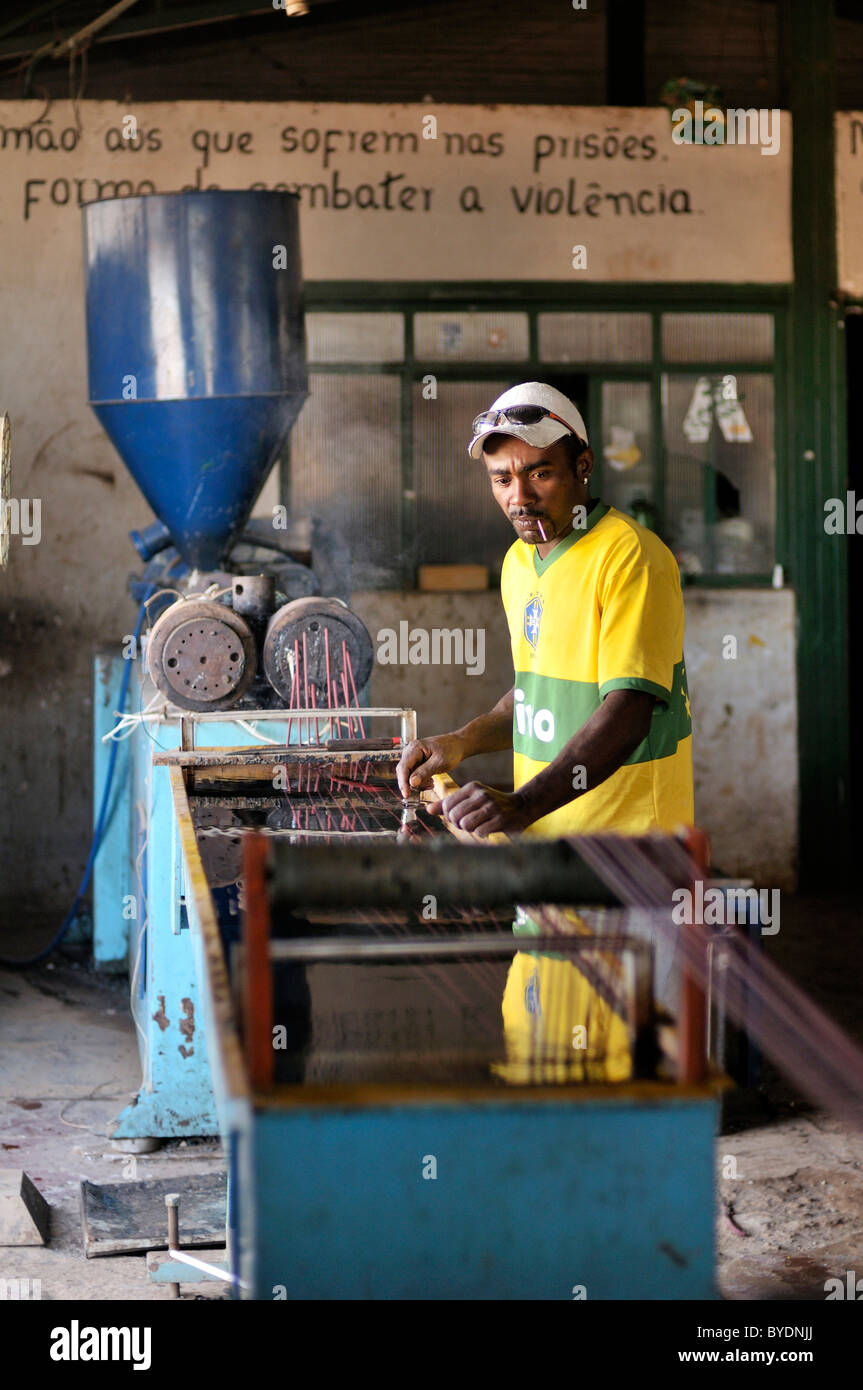 Worker at the process of melting and hardening used plastics in the social project for ex-prisoners 'Reintegar - Stock Image