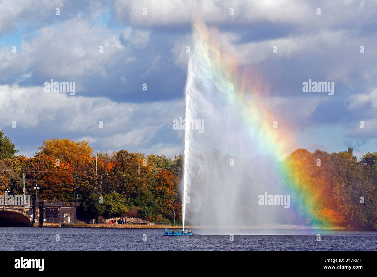 Alster fountain, water fountain with a rainbow on the Inner Alster lake in the center of the Hanseatic city of Hamburg Stock Photo