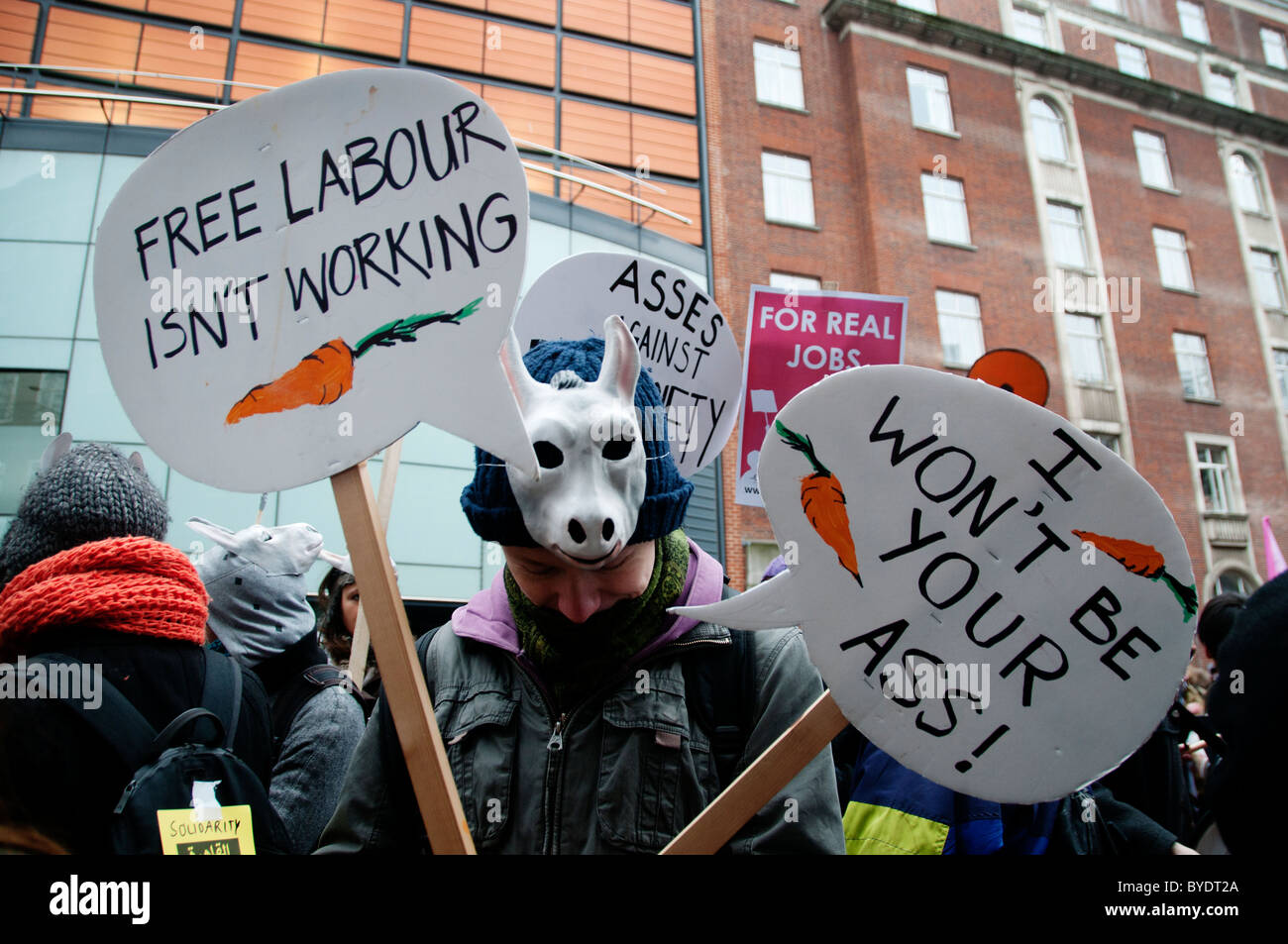 Demonstration against education cuts. Protesters with donkey  masks and carrots with placards - Stock Image