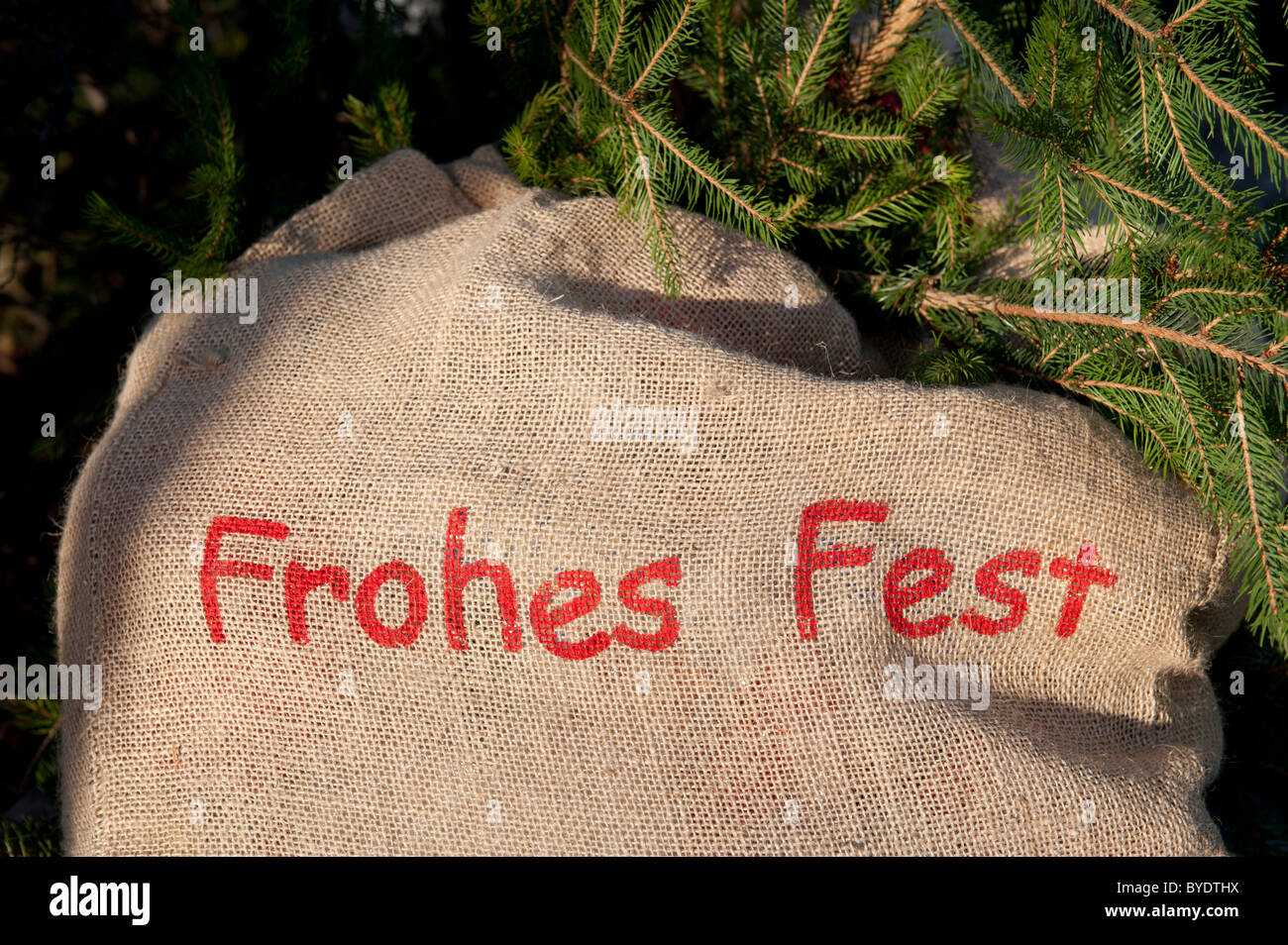 Frohes Fest or Merry Christmas, red lettering on a sack, spruce branches Stock Photo