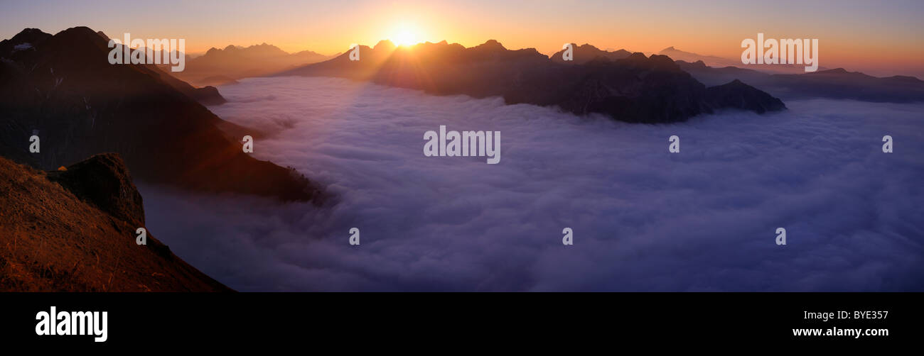 Mountain valley under fog with mountain peaks in the evening light, Allgaeu Alps, Kleinwalsertal valley, Vorarlberg, - Stock Image
