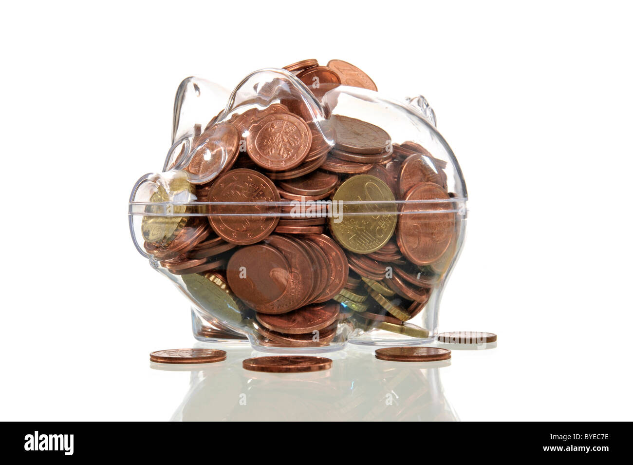 Over-filled transparent piggy bank, symbolic image for full coffers - Stock Image