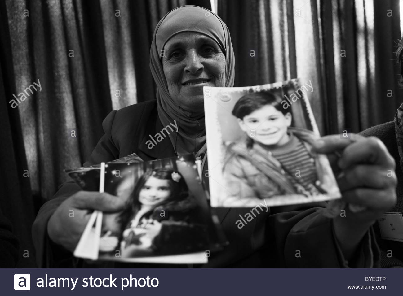 A Palestinian woman holding family photographs in the West bank Israel - Stock Image
