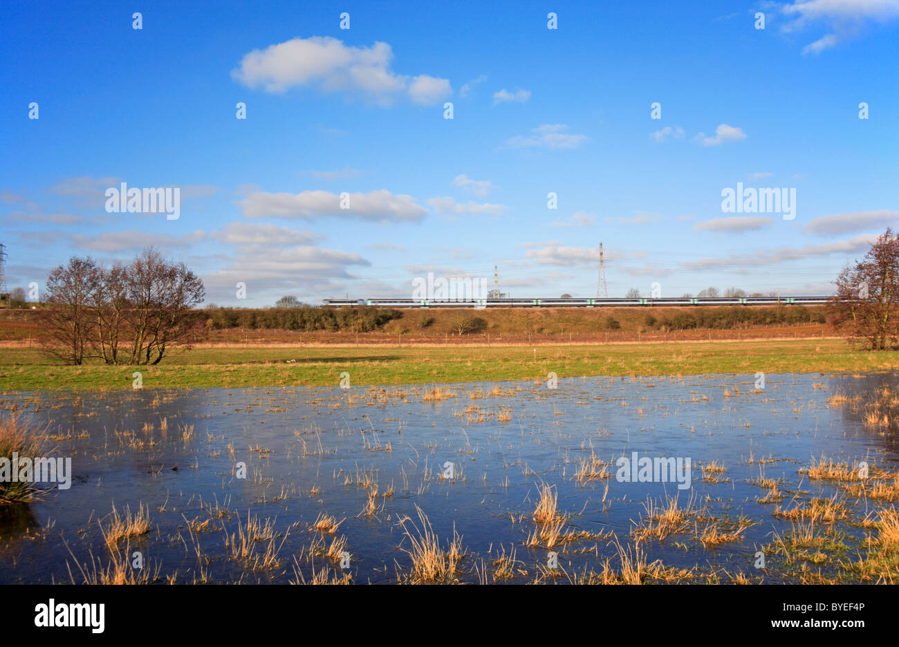 A frozen flooded meadow at Caistor St Edmund, Norfolk, England, United Kingdom, with an InterCity train in the background. - Stock Image