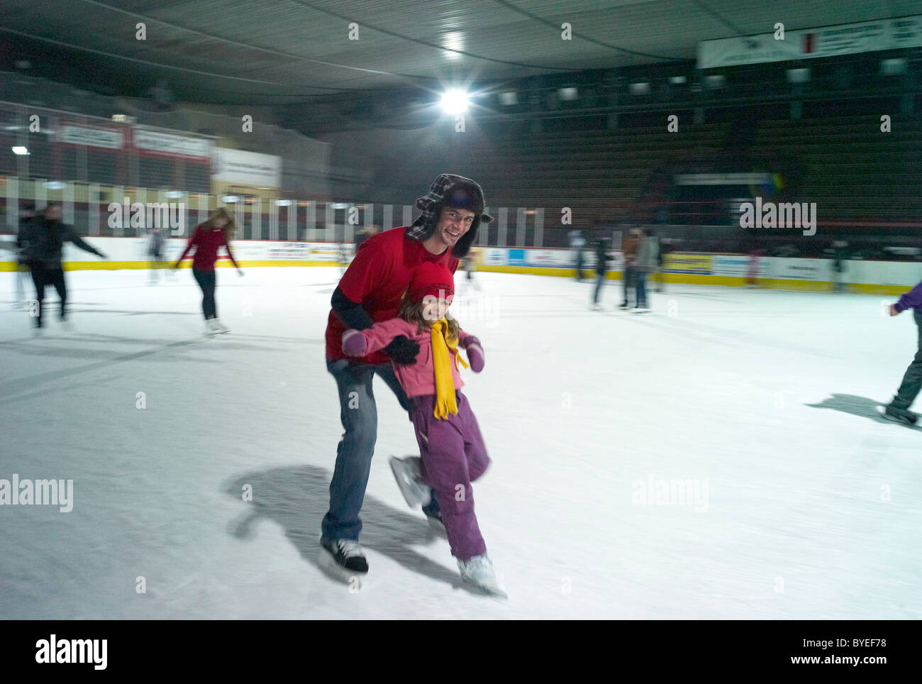 A young man teaches a child to skate on an ice rink in Nove Zamky Slovakia - Stock Image