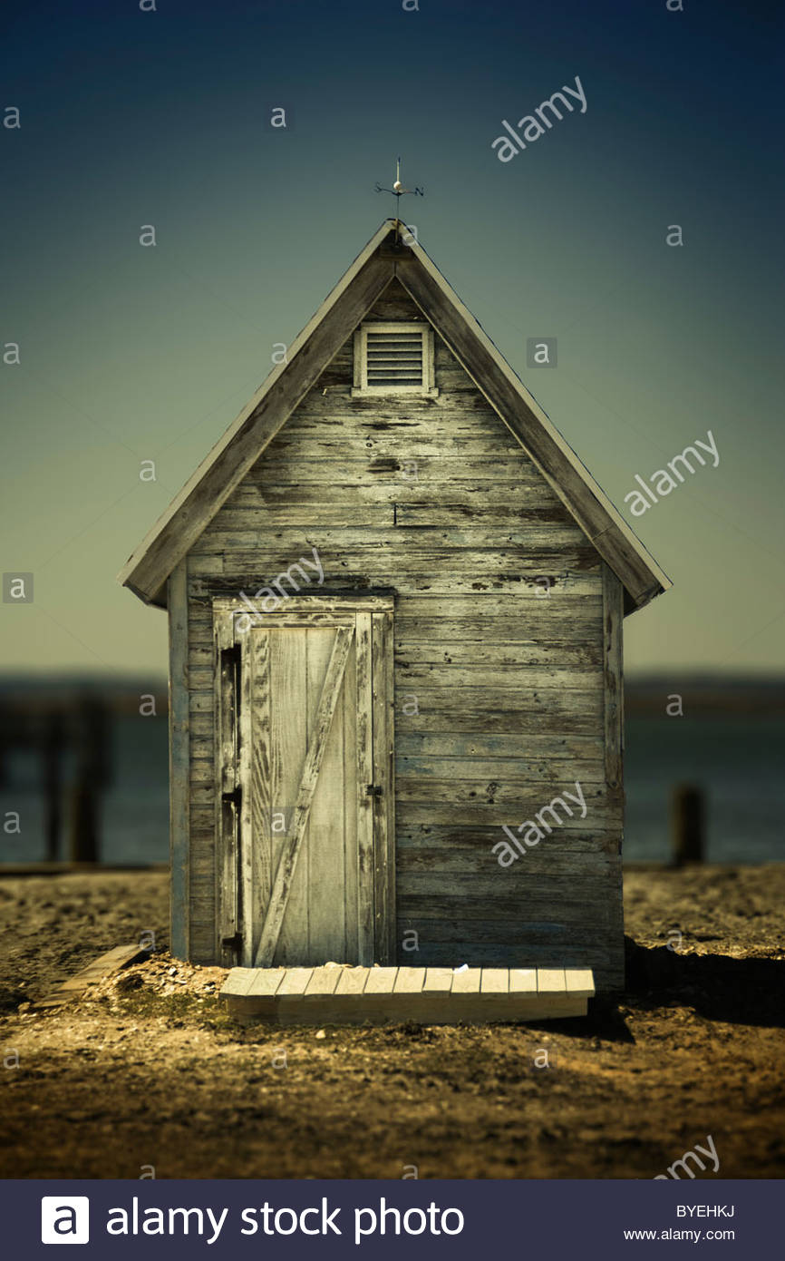 Weathered fishing shed on beach in summer - Stock Image