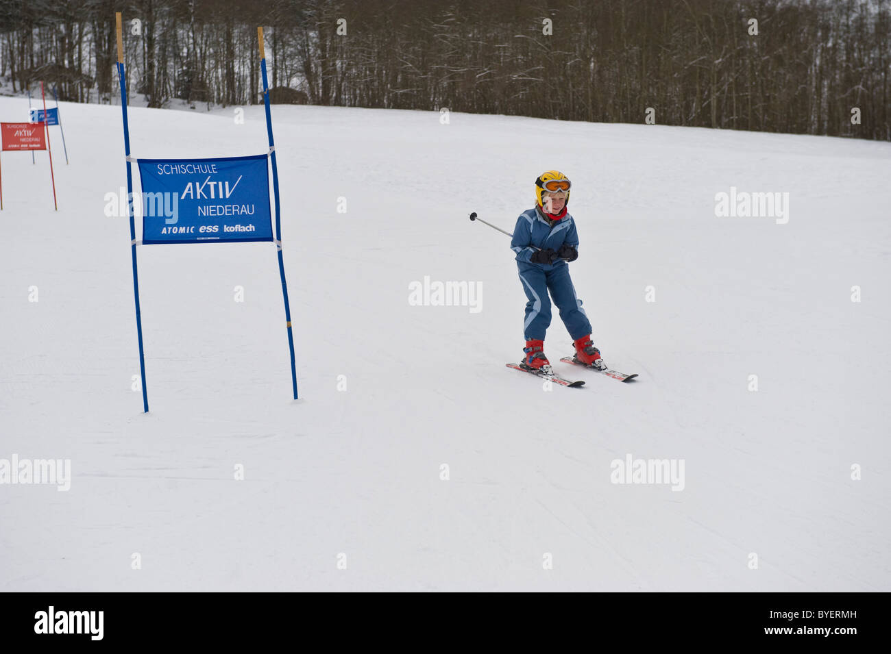 Young boy participating in a beginners slalom race in Niederau in Austria - Stock Image
