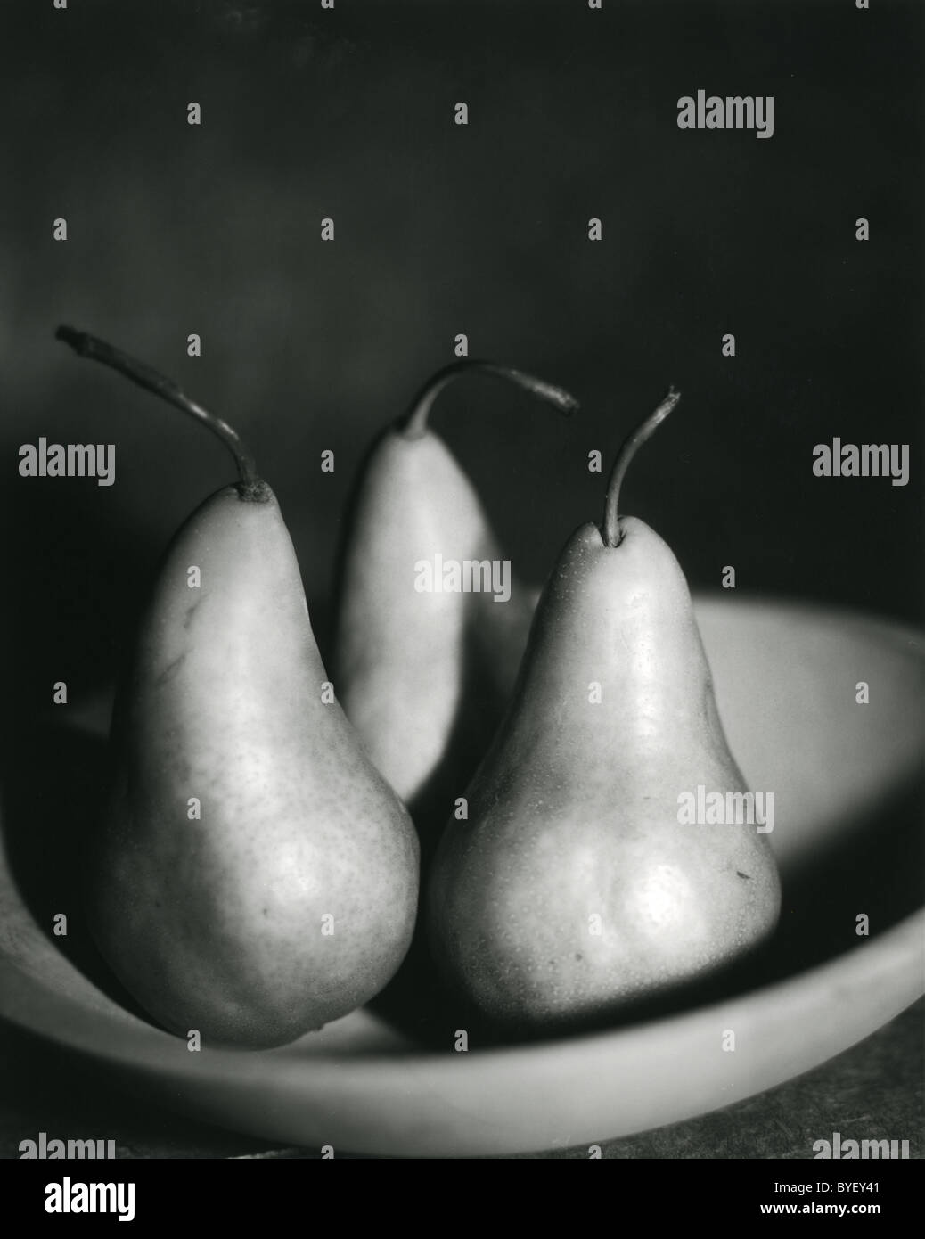 black and white photo of three pears in a wooden bowl - Stock Image