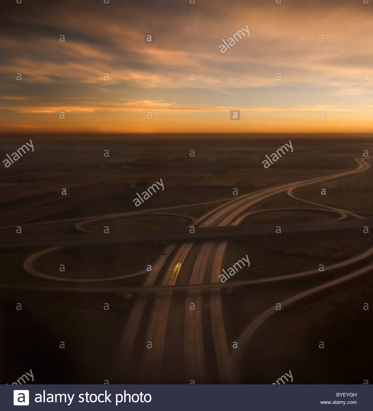 High view over modern road junction with setting sun - Stock Image