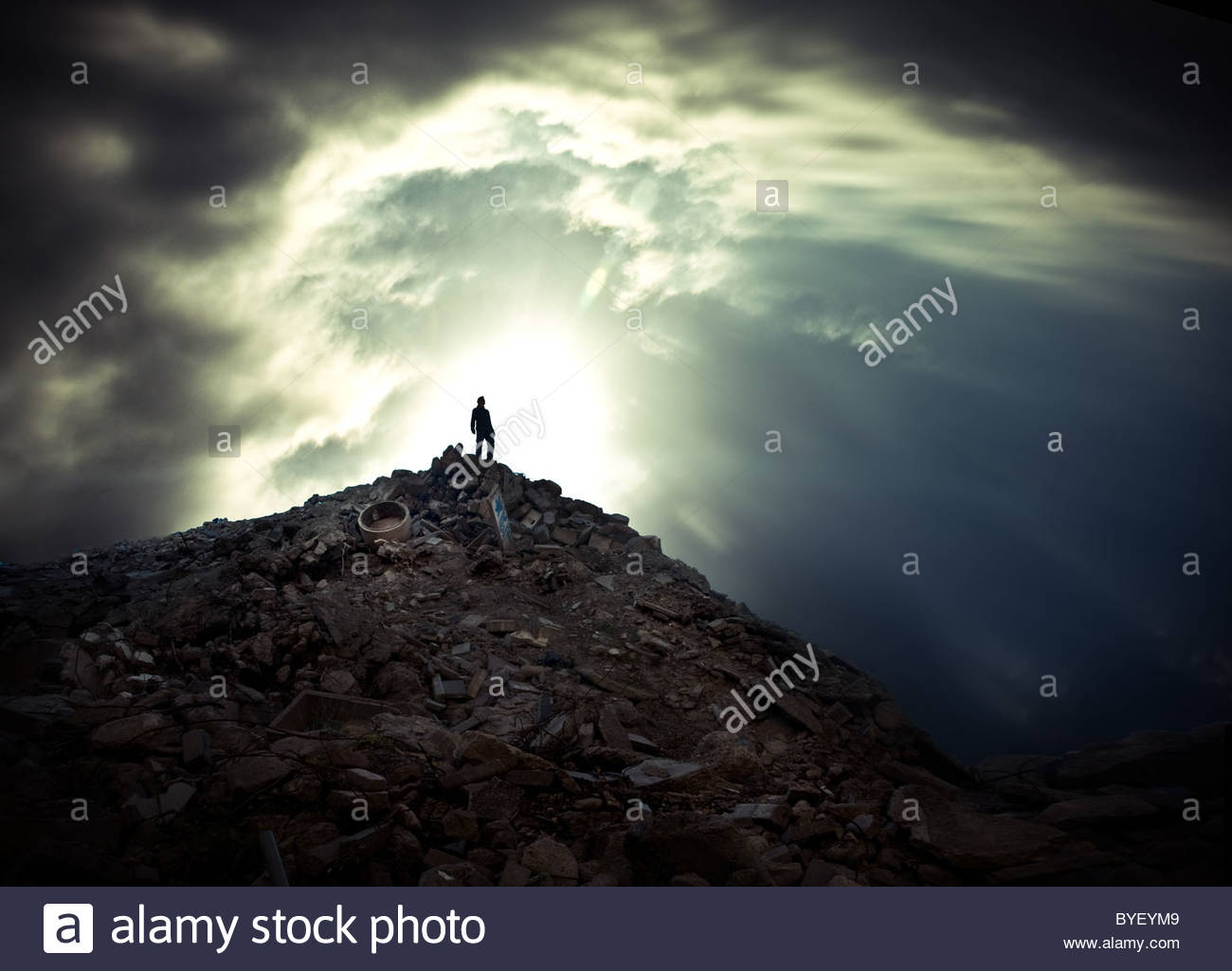 Lone male figure standing on the top of a mountain of waste - Stock Image