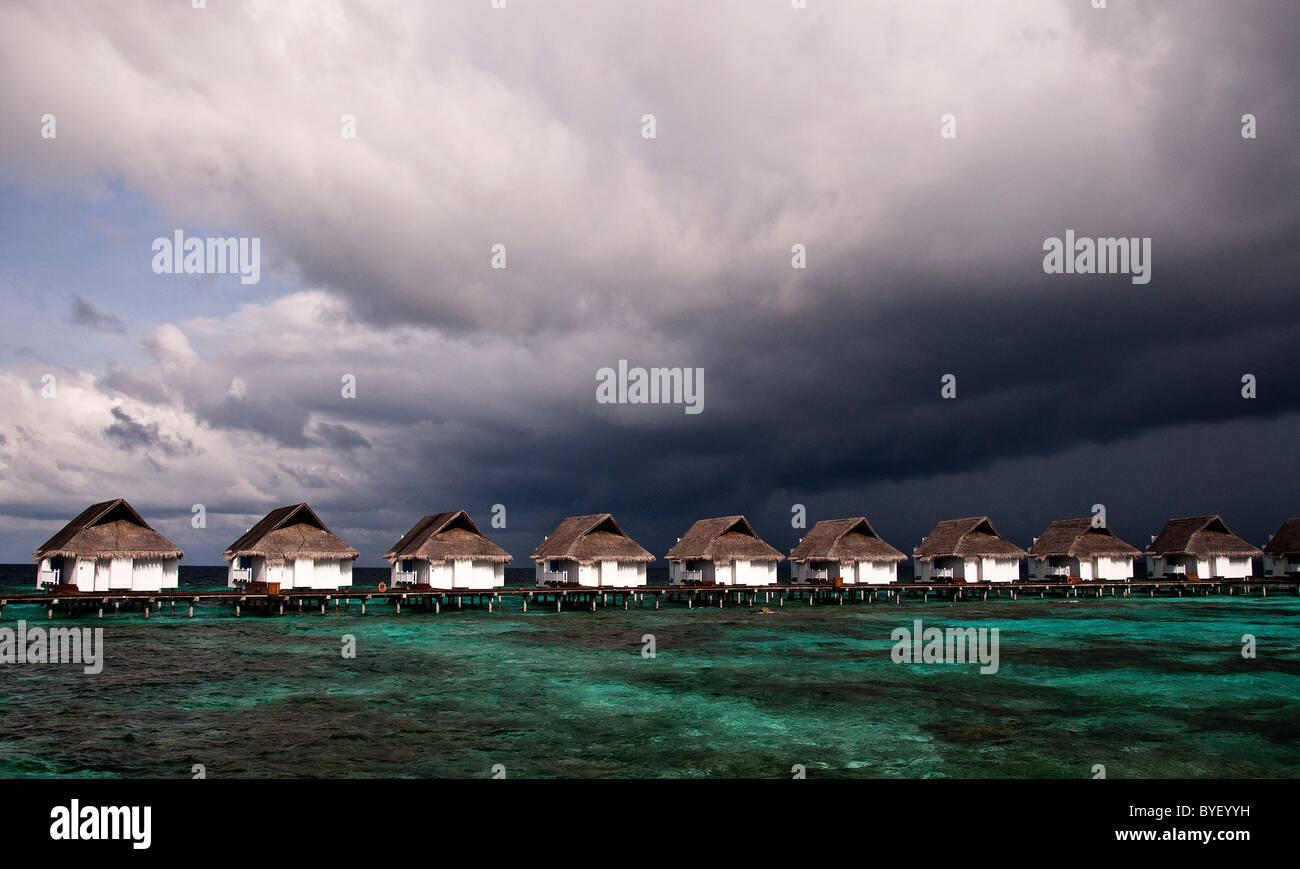 grand centara island maldives white sands blue sky turquoise sea honeymoon storm clouds building thunderstorm - Stock Image