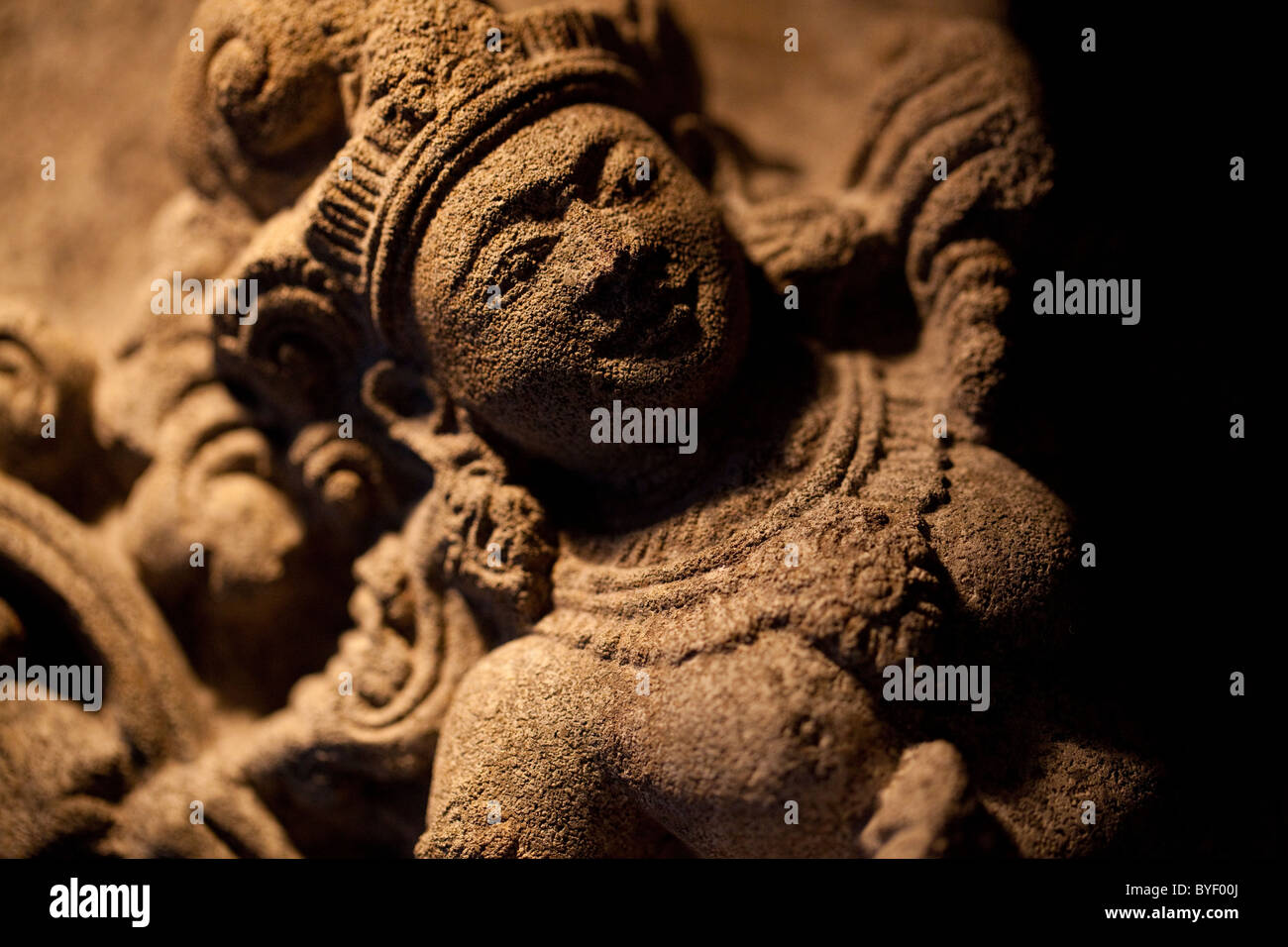 Detail of a busty Indian dancer or deity on a relief sculpture - Stock Image
