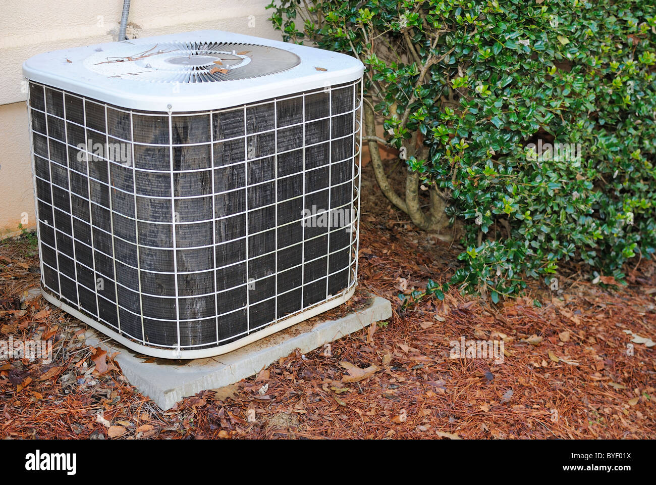 Residential air condition unit in mulch near a home. - Stock Image
