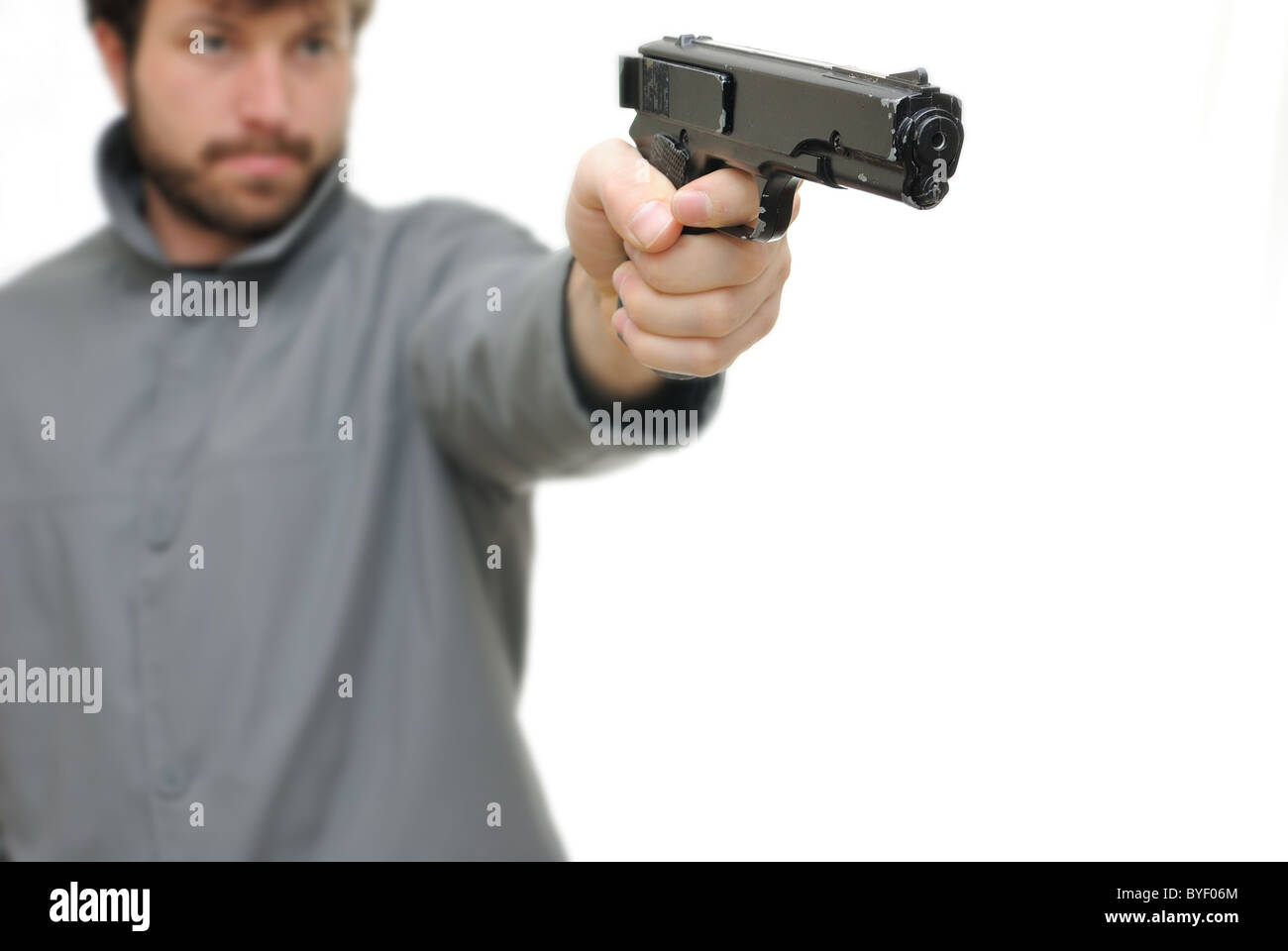 Man pointing a gun isolated on white background. - Stock Image