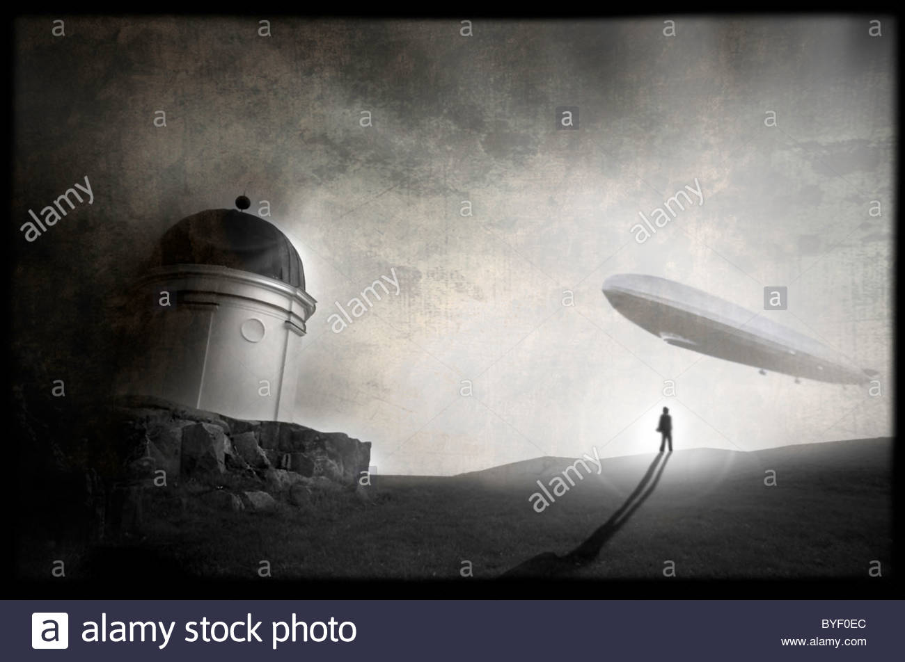 A man standing close to a cliff is looking at a zeppelin flying towards him - Stock Image