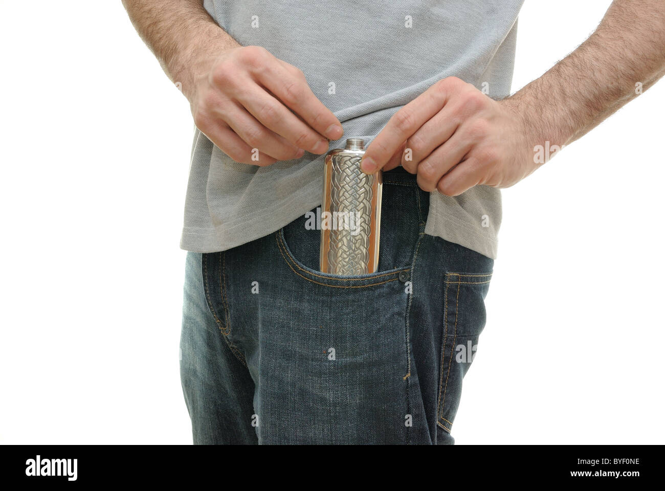 A guy pulling and uncapping a flask from his pocket - Stock Image