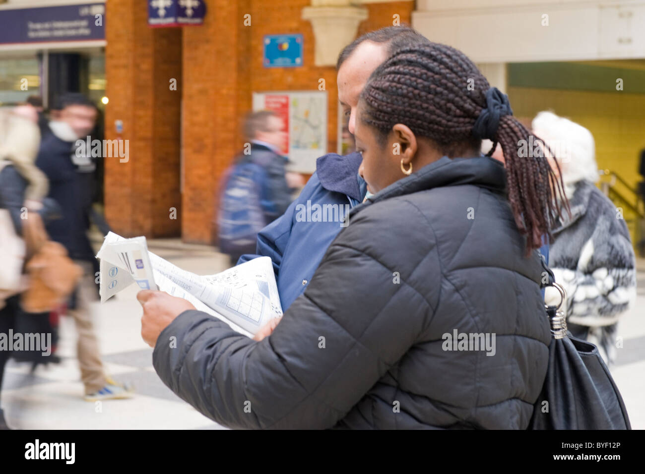 London , Liverpool Street Station , pretty Afro Caribbean young girl with braided or beaded plaited hair asking - Stock Image