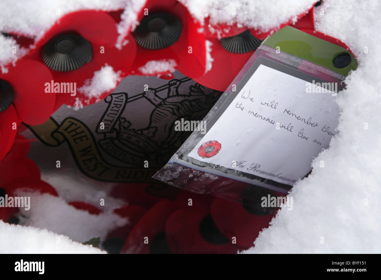 Poppy wreath in snow with card saying 'We Will Remember Them. The Memories Will Live On' - Stock Image