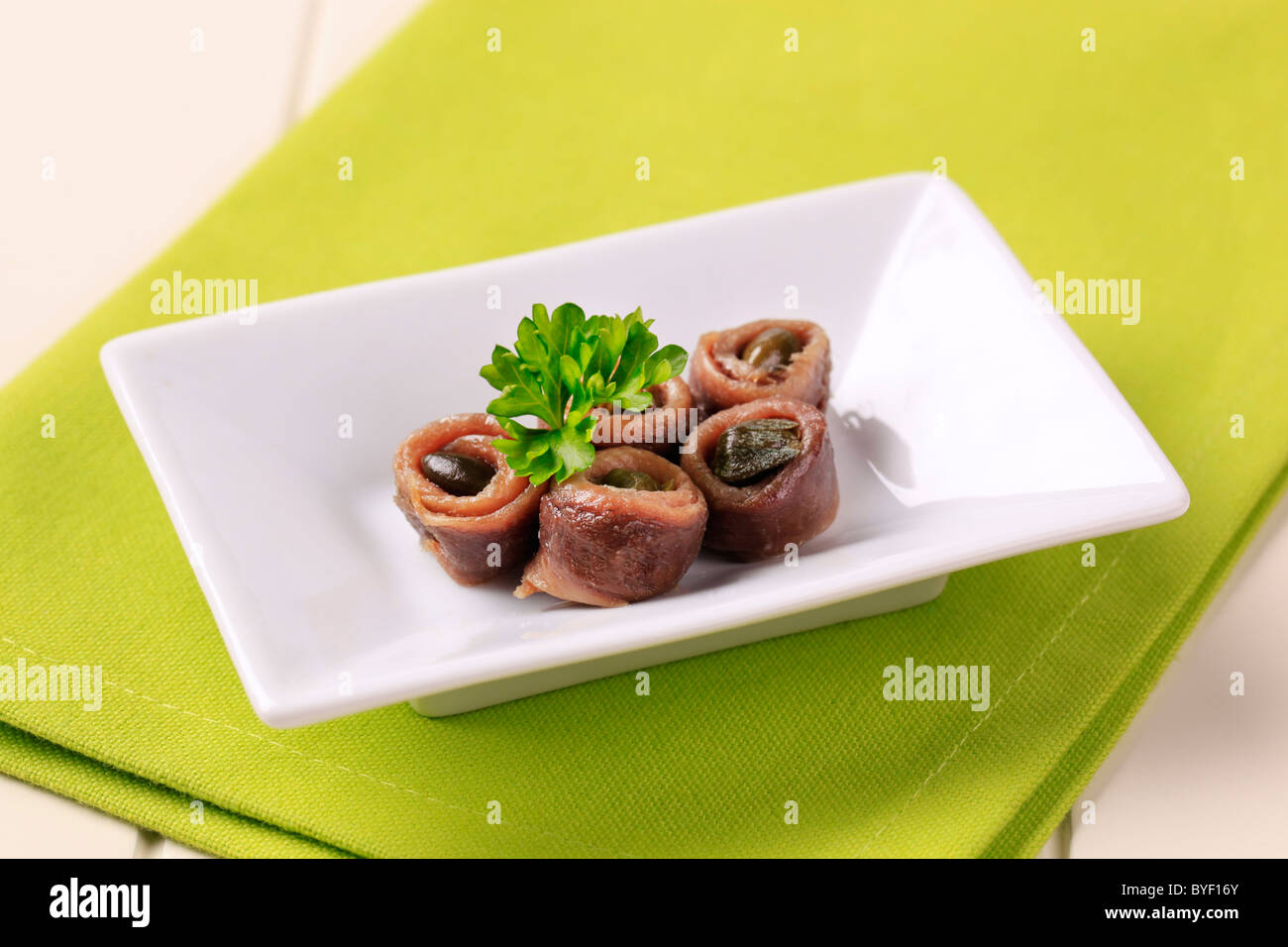 Rolled up anchovy fillets filled with capers - Stock Image