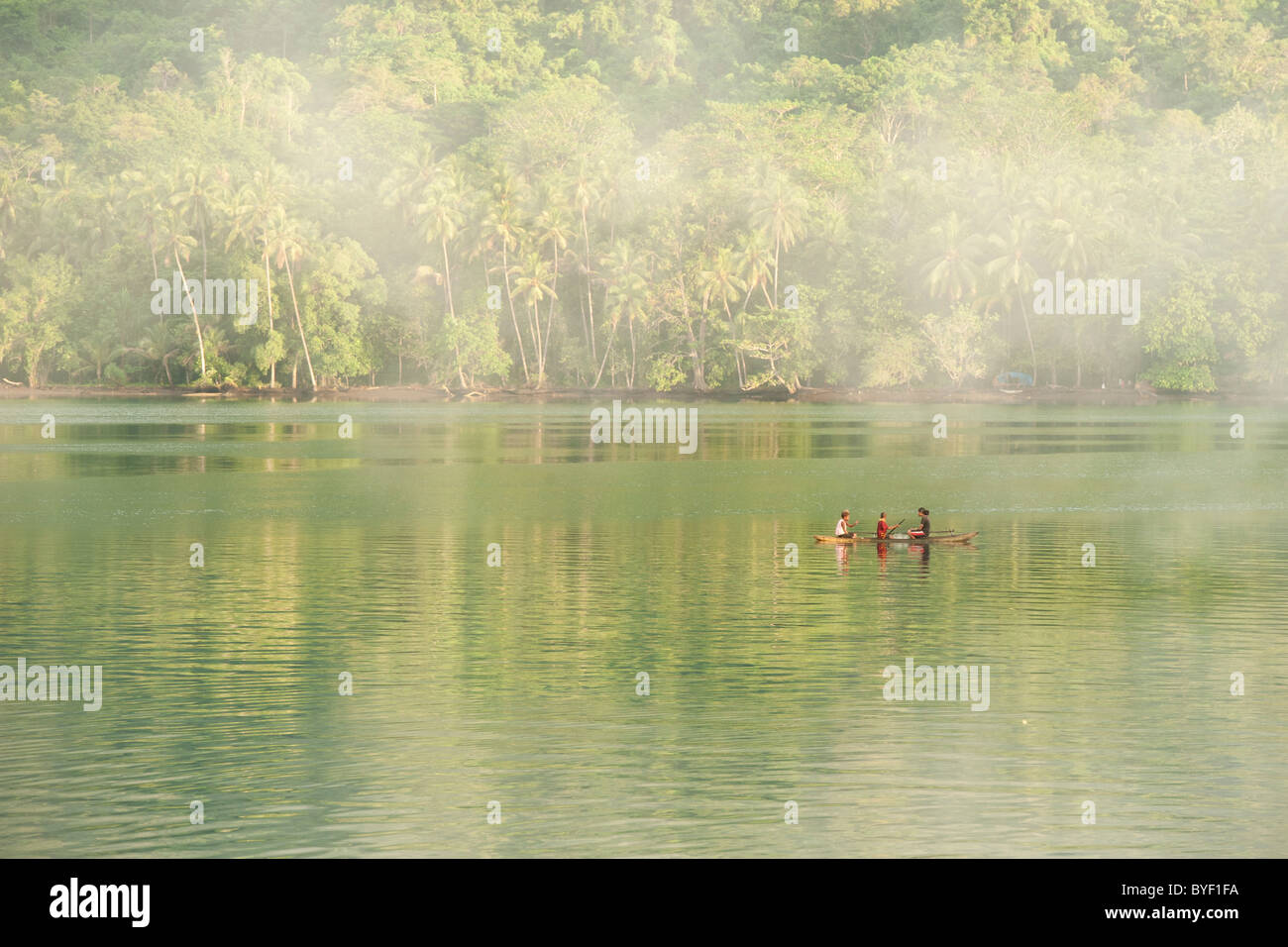 Papua New Guinea family paddling in traditional outrigger canoe on misty morning - Stock Image