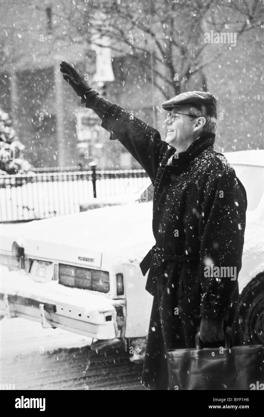 Businessman Hailing Cab in Snowstorm, NYC - Stock Image