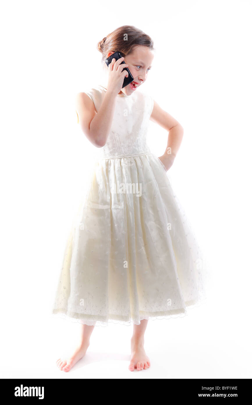 Young girl in white dress talking and texting against a white background. - Stock Image