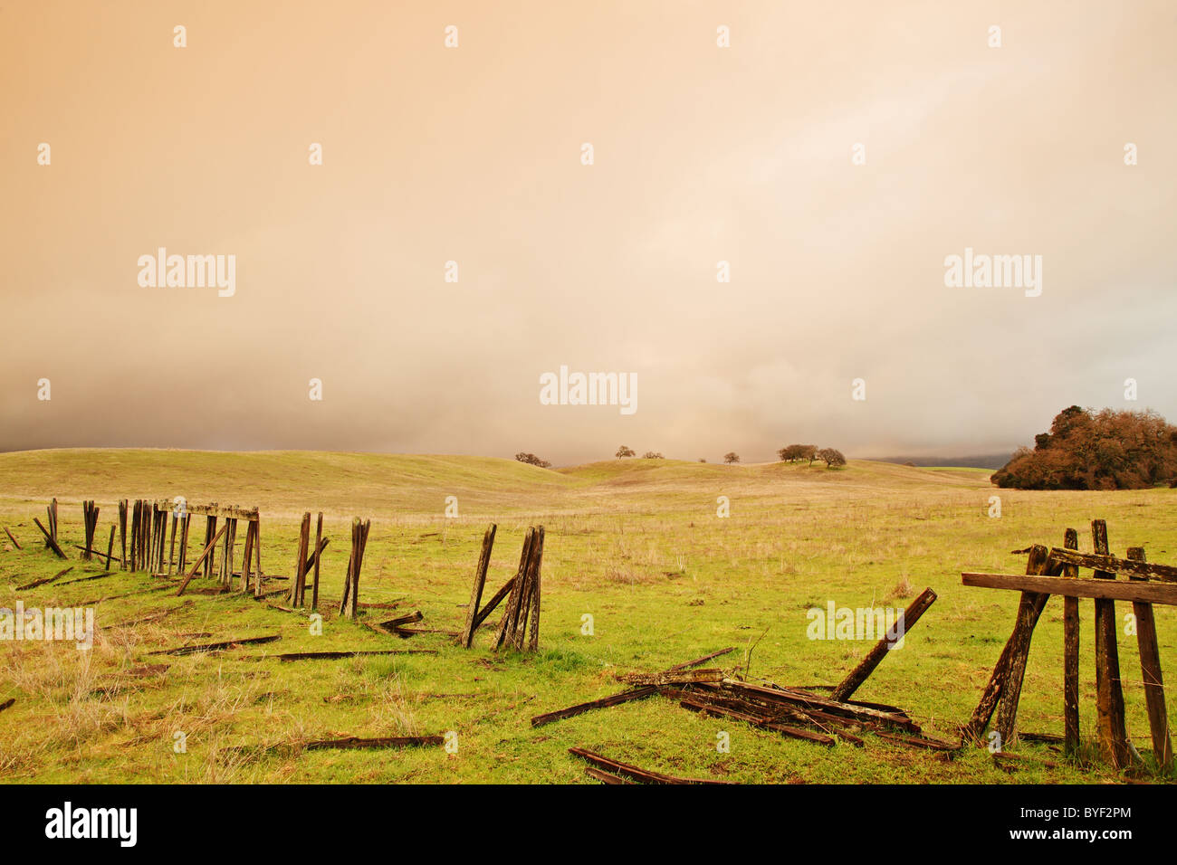 A broken wooden farm fence on a stormy day. - Stock Image