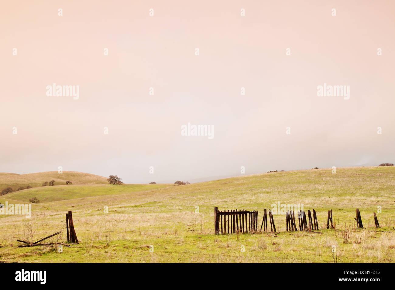 A broken farm fence opens into farmland - Stock Image