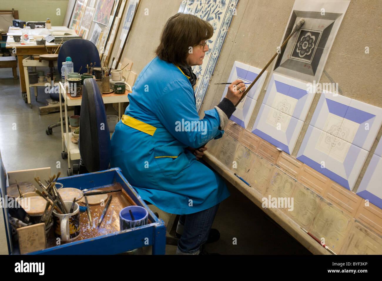 Woman hand apinting a tile design at Viúva Lamego factory near Sintra, Portugal - Stock Image