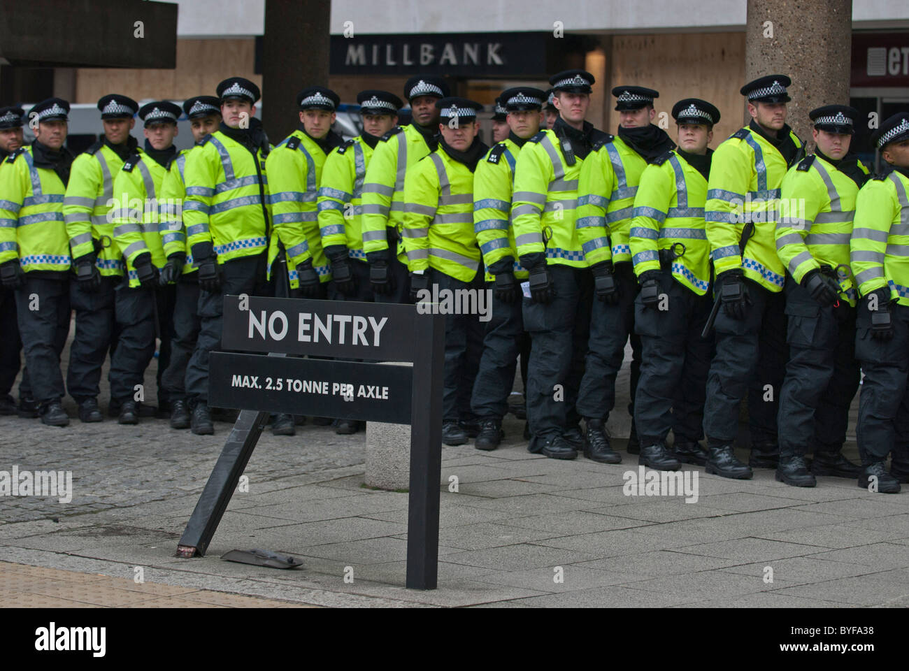 Long line police officers protecting Conservative HQ Millbank Centre from student and teacher protesters on education - Stock Image