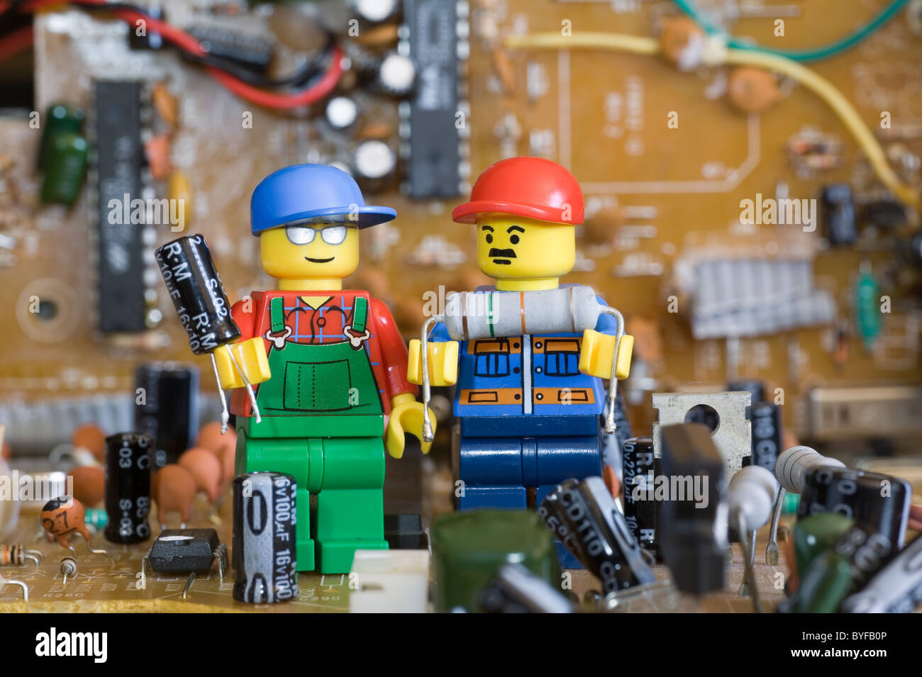 lego engineers in electronic circuit land holding components stock