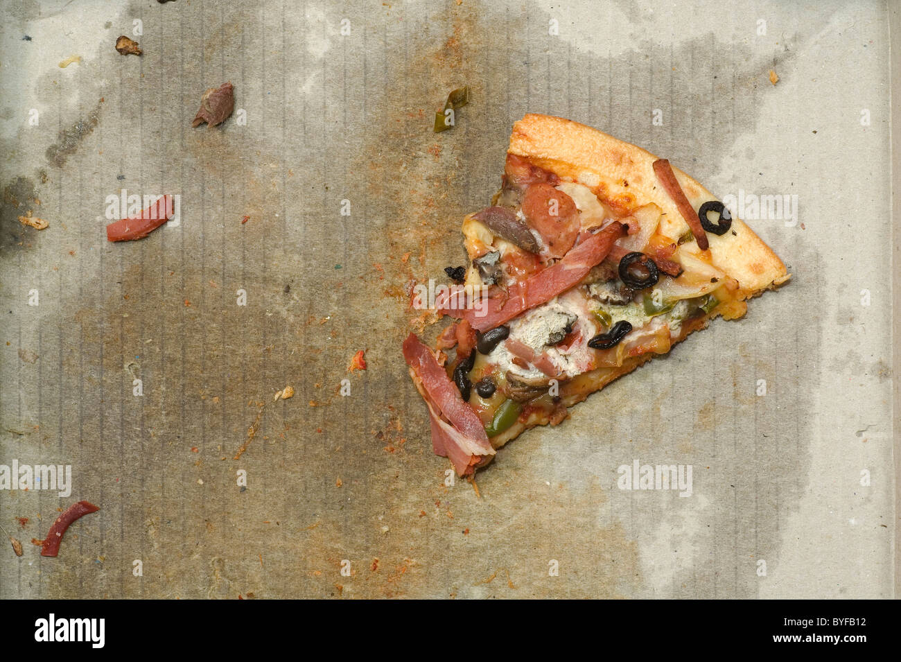 A slice of cold greasy and mouldy pizza in an old pizza box. - Stock Image