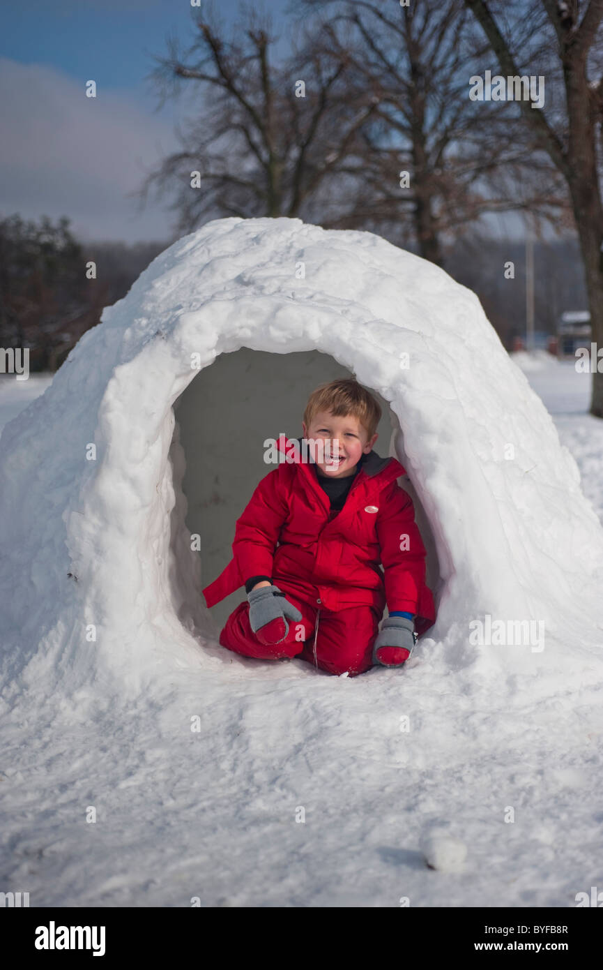 A boy sits in the entrance of an igloo. - Stock Image