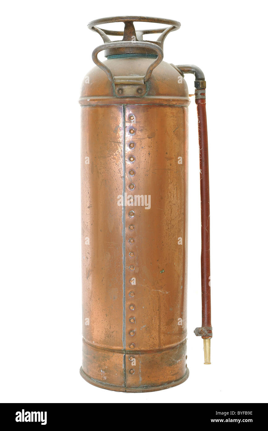 An antique fire extinguisher isolated on a white background. - Stock Image