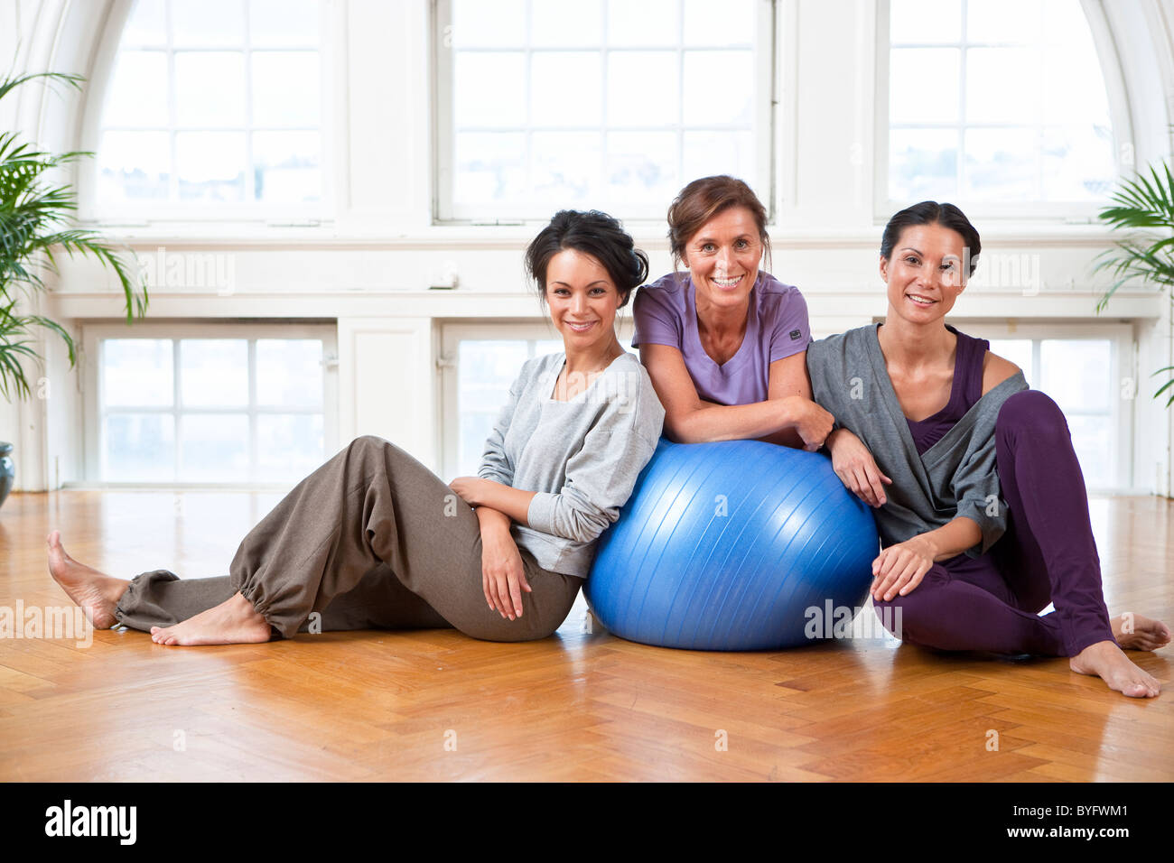 Portrait of three women with fitness ball in gym - Stock Image