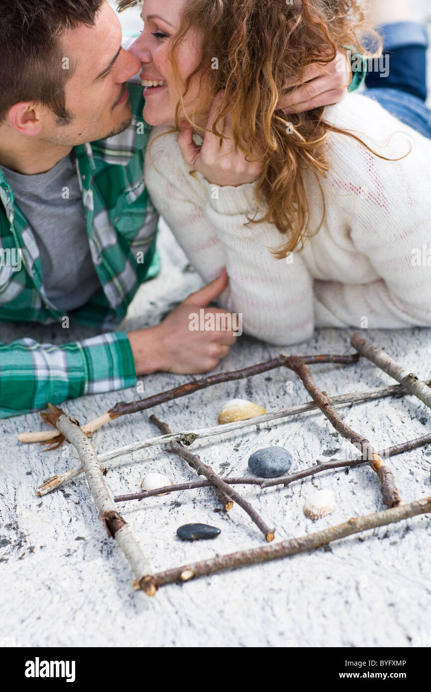 Mid adult couple playing tic-tac-toe on beach, close to kissing - Stock Image