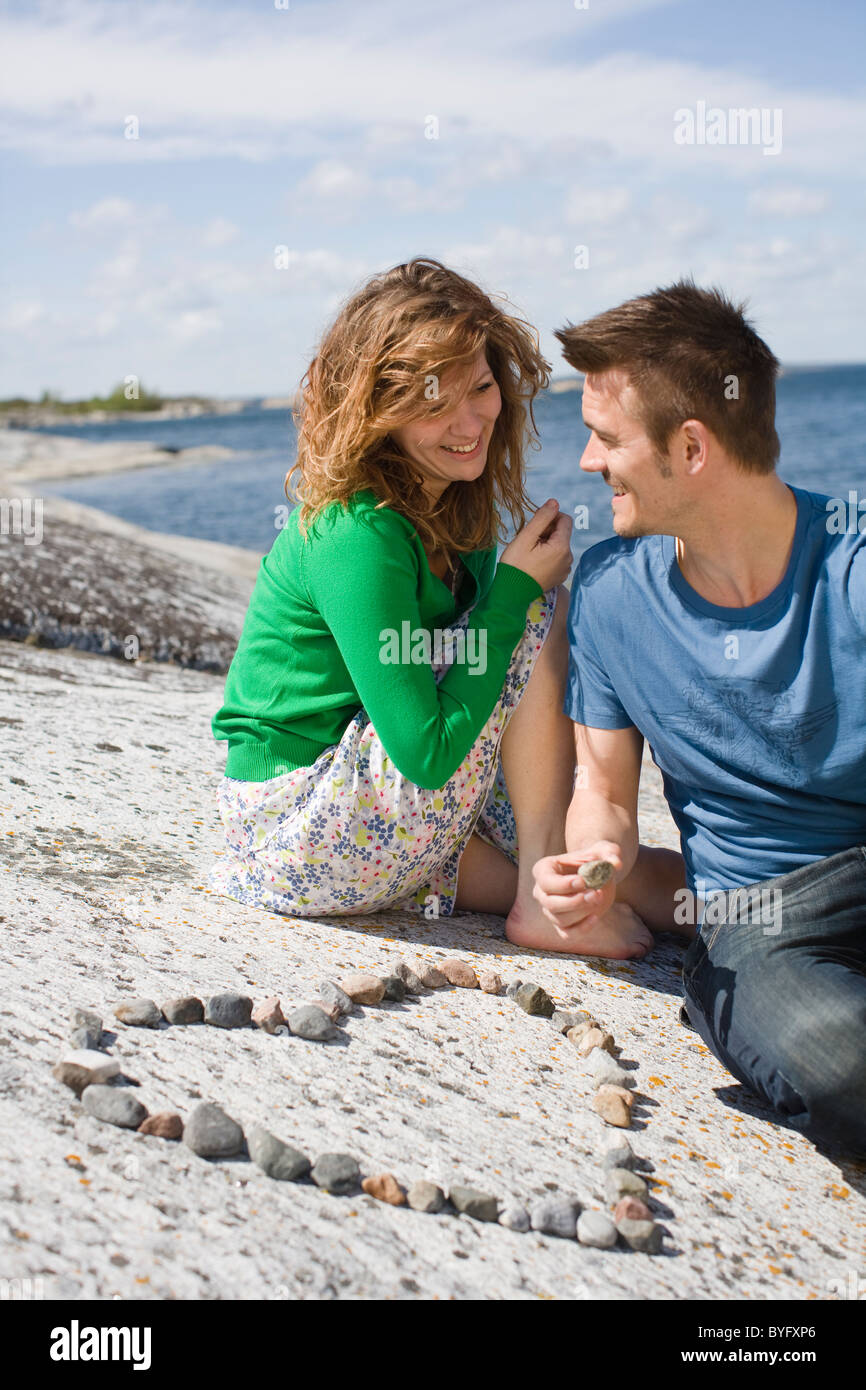 Mid adult couple sitting on beach near heart made from pebbles - Stock Image
