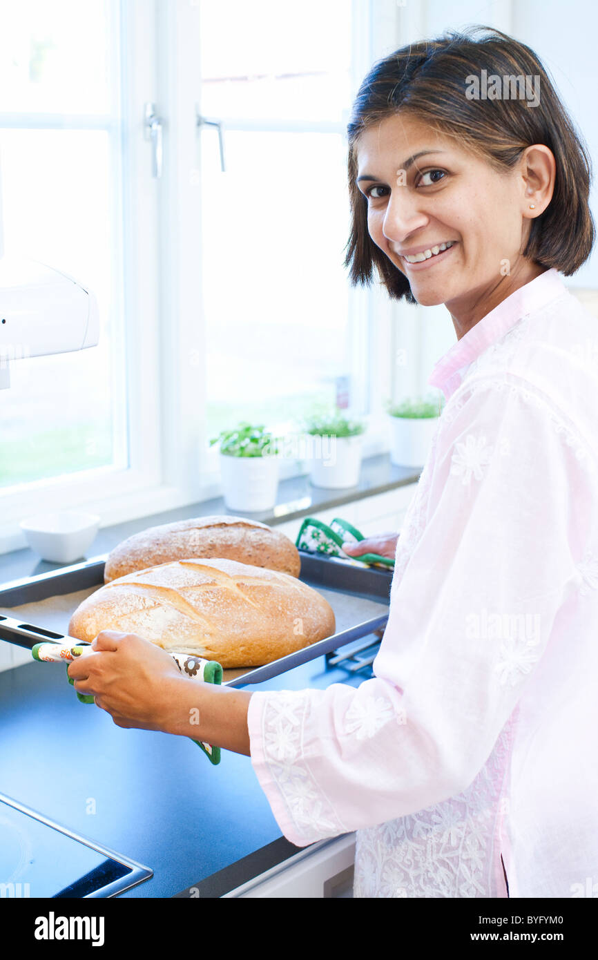 Portrait of woman holding bread on tray in kitchen - Stock Image