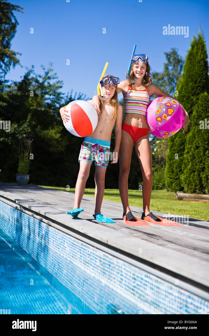 Sisters in scuba masks and flippers near swimming pool - Stock Image
