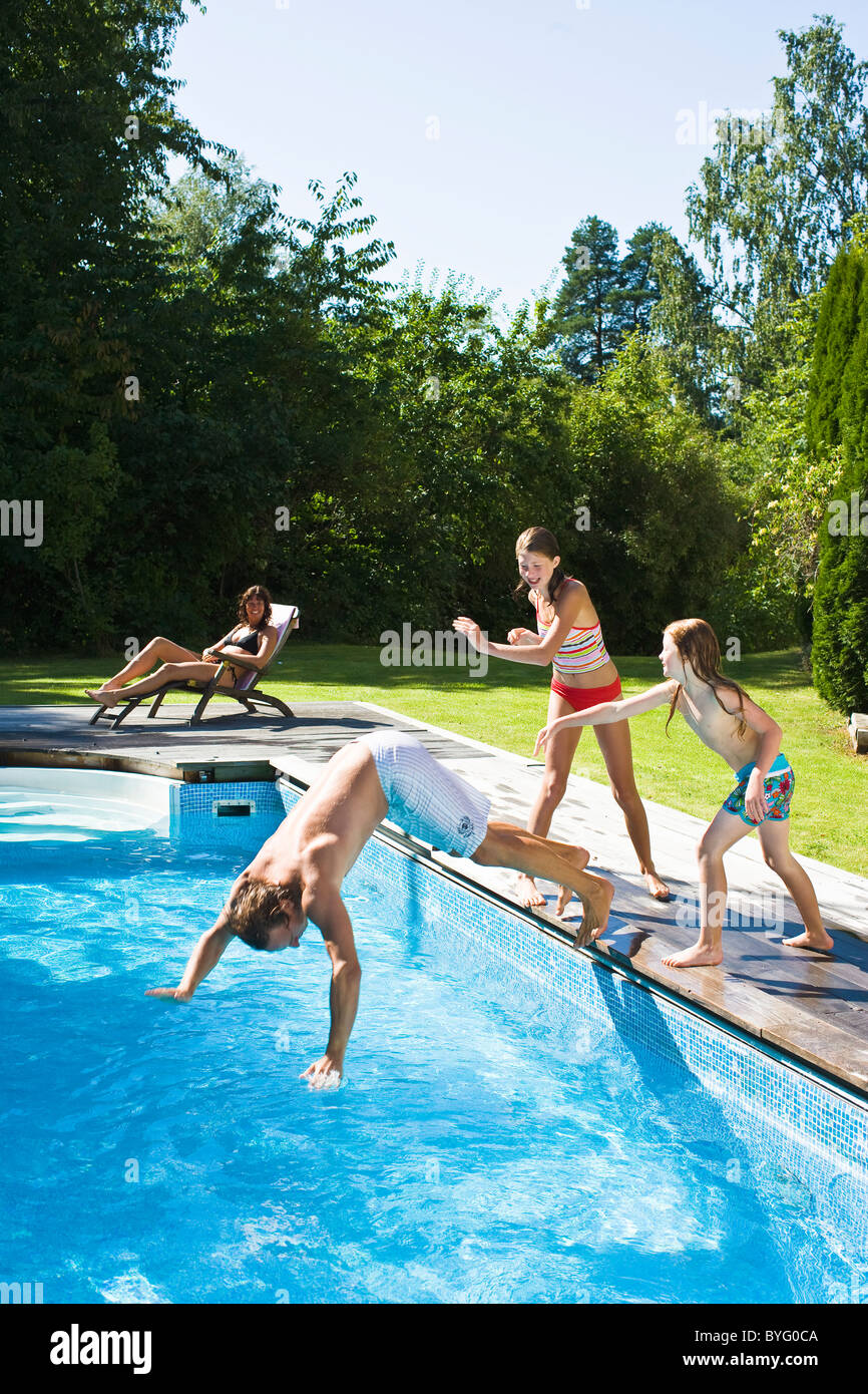 Children pushing father into swimming pool - Stock Image