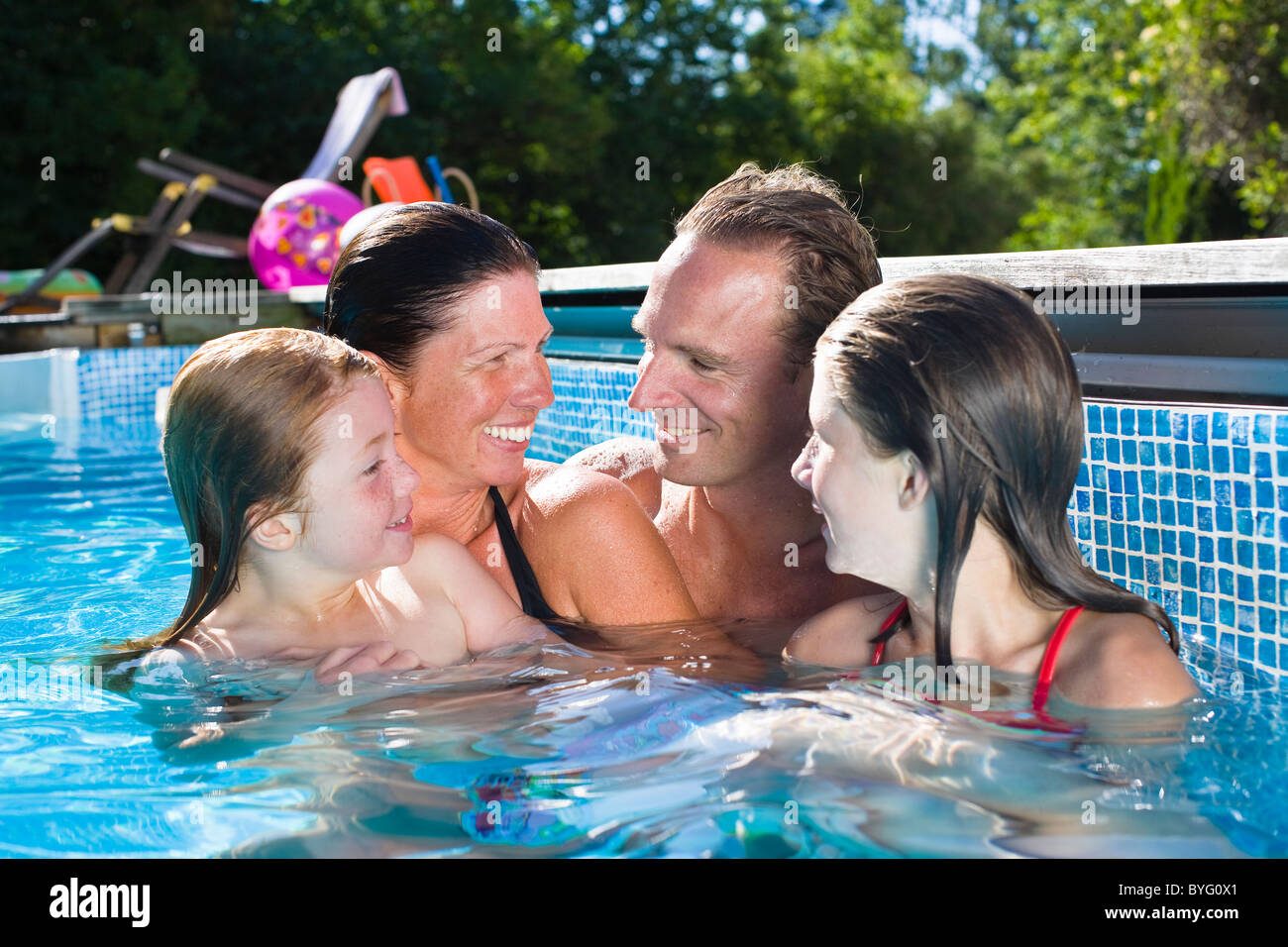 Couple with children in swimming pool - Stock Image