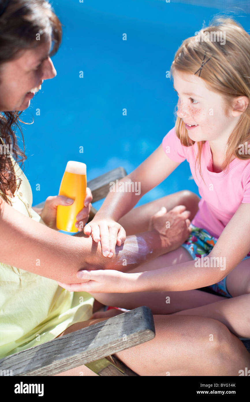 Daughter applying suntan lotion on her mothers arm - Stock Image