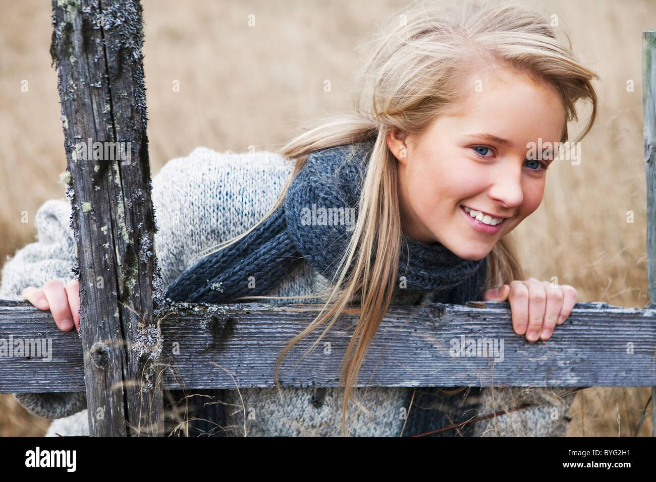 Portrait of teenage girl wearing scarf in field - Stock Image