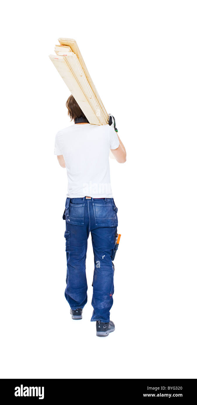 Studio shot of carpenter carrying lumber - Stock Image