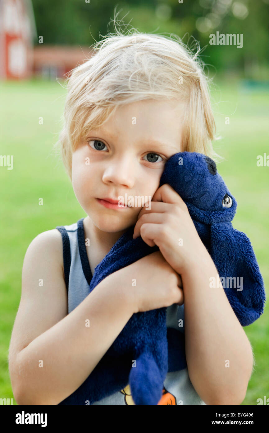Portrait of boy hugging toy - Stock Image