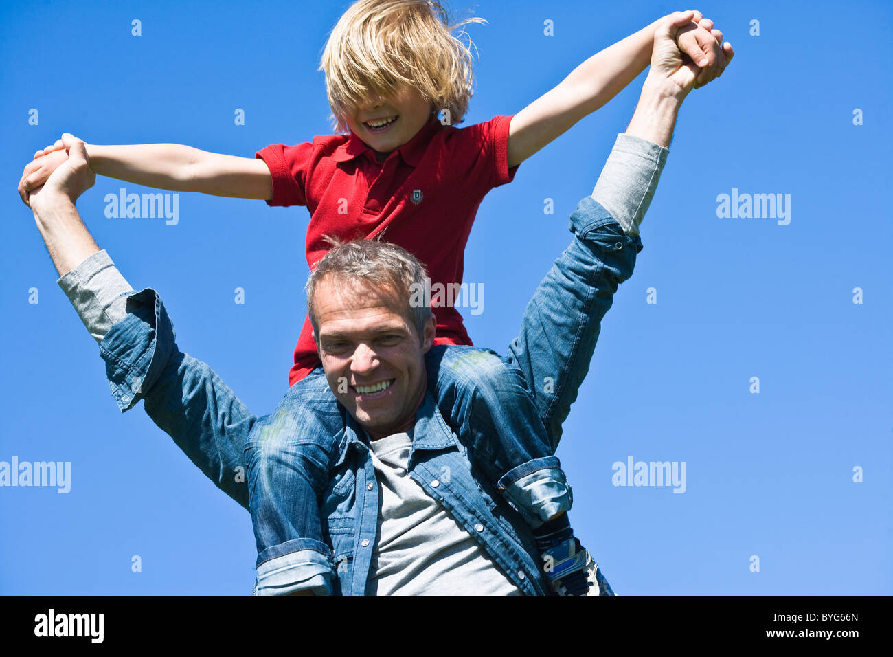 Piggyback portrait of father and son against clear sky, in bright sunlight - Stock Image