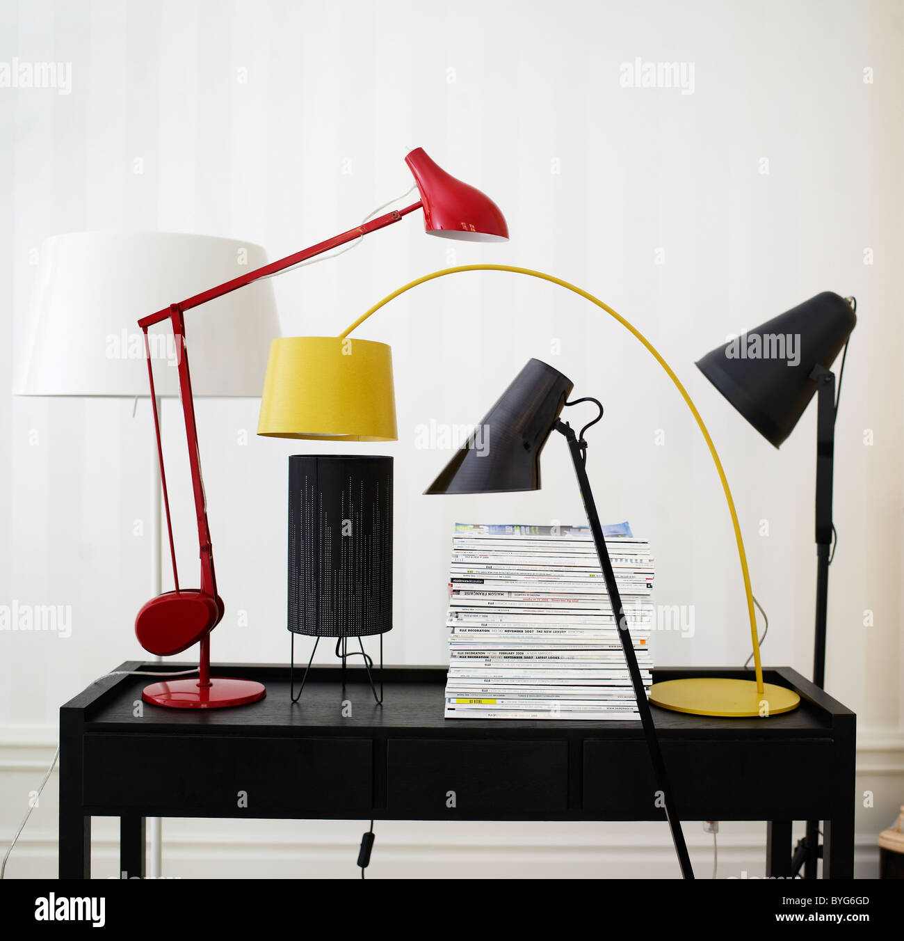 Variety of modern design lamps on top of desk - Stock Image