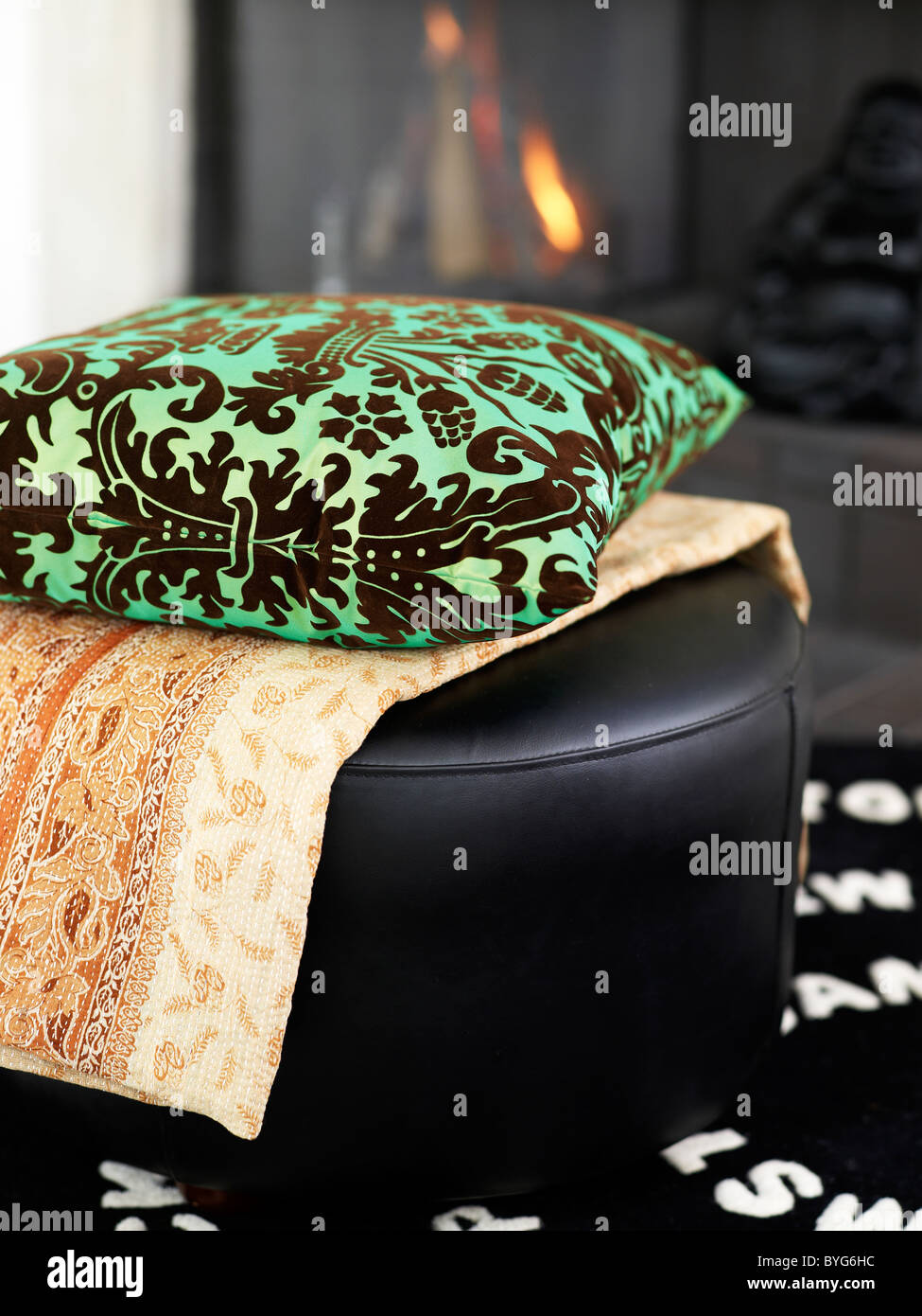 Still-life with ornate cushion and cloth on top of black leather hassock - Stock Image